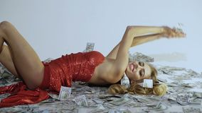 Trotse vrouw in elegante rode kleding die op bankbiljetten liggen Rijke vrouw Bedrijfs concept Vrouw met partij van geld Het geld stock videobeelden