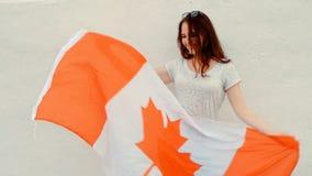 Trotse vrouw met de vlag van Canada en het brede glimlach dansen Portret van een mooie jonge vrouw die van het gemberhaar pret he stock video