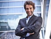 Trotse Zakenman die voor zijn bureau glimlachen Stock Foto