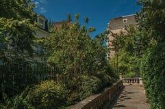 Trottoar i skogsbevuxna trädgårdar av andelsfastigheter under solig blå himmel på Montmartre i Paris royaltyfri fotografi