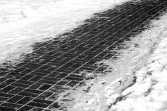 Trottoar och snö på dess sida i svartvitt Arkivfoton