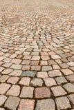 Trottoaren som fodras med den kulöra granitstenen i stadfyrkanten Texturera bakgrund royaltyfri bild
