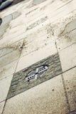 Trottoir avec la couverture de trou d'homme d'égout Image stock