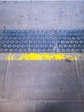 Trottoir avec la ligne jaune et le métal ouvré Photo stock