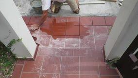 Trottoir carrelé de restauration étendant des tuiles dans le bâtiment clips vidéos