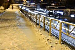 Trottoir dans la neige et routes urbaines avec des voitures dans le mouvement le soir Lumières brouillées photos stock