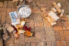 Trottoir en construction avec la pile des pavés, le seau rempli de cailloux, la truelle, et les gants image stock