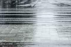 Trottoir et route goudronnée humides pendant la pluie photographie stock libre de droits