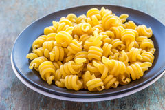 Trottole Pasta. On a black plate. Raw  on wooden plank. Popular Italian pasta - raw and uncooked Royalty Free Stock Image