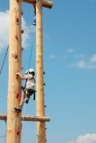 Trotzen Sie dem kleinen Jungen, der oben auf einem hölzernen Pfosten für die Kinder klettert, die Übungen klettern Stockbild