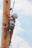 Trotzen Sie dem kleinen Jungen, der oben auf einem hölzernen Pfosten für die Kinder klettert, die Übungen klettern Stockfotos