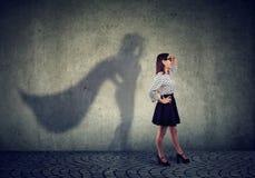 Trotzen Sie der jungen Geschäftsfrau, die als Superheld aufwirft lizenzfreie stockfotos