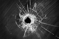 Trou criqué tiré par balle sur le verre de fenêtre cassé Images libres de droits
