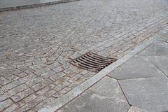 Trou d'homme d'égout de drainage dans la ville automnale couverte Une couverture de trou d'homme dans la ville, automne Photos libres de droits