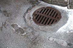 Trou d'homme d'égout sur l'asphalte urbain Image libre de droits