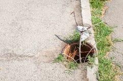 Trou d'homme ouvert dangereux sur le passage couvert ou le trottoir de piétons Images stock