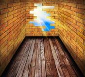 Trou dans le mur de briques de la pièce avec l'étage en bois Photographie stock libre de droits