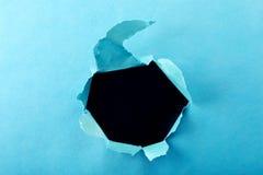 Trou dans le papier avec les côtés déchirés Photographie stock libre de droits