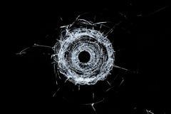 Trou de balle simple en verre cassé en verre d'isolement sur le noir photo stock