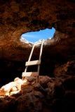 Trou de caverne de cap de Barbaria avec l'échelle rustique sur le bois Photographie stock libre de droits