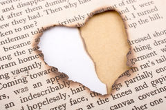 Trou de forme de coeur brûlé sur le papier Images stock