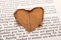 Trou de forme de coeur brûlé sur le papier Photos stock