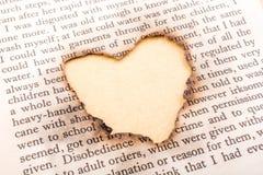 Trou de forme de coeur brûlé sur le papier Photo libre de droits