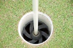Trou de golf avec le bâton de drapeau. Images libres de droits