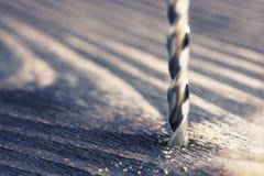 Trou de perçage de peu de foret dans la planche en bois Images libres de droits