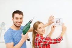 Trou de perçage de sourire de couples dans le mur à la maison Photos libres de droits