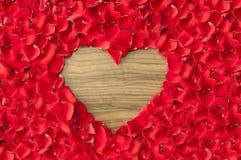 Trou en forme de coeur dans des pétales de rose - amour et fond de valentine Photo stock