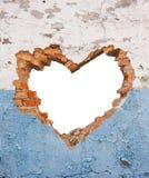 Trou en forme de coeur dans le vieux mur de briques Photos stock