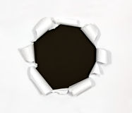 Trou rond en papier sur le fond noir Images stock