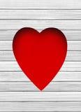 Trou rouge de coeur dans en bois blanc Images libres de droits