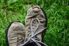 Trou sur une espadrille grise sur un pied dans l'herbe Photographie stock libre de droits