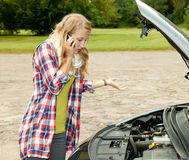 Trouble with the car engine in the road. Young woman phoning to help Royalty Free Stock Photo