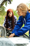 Trouble with the car engine in the road. Woman car mechanic repairs engine damaged car, trouble with the car engine in the road Royalty Free Stock Photos