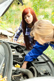 Trouble with the car engine in the road. Woman car mechanic repairs engine damaged car, trouble with the car engine in the road Royalty Free Stock Image