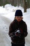 Trouble in the Making. Young Boy contemplating what to do with his snowball once perfected Stock Photos