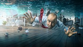 Trouble in office. Businessman swimmin a flooded office royalty free stock photo