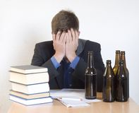 Troubled. Businessman with books, papers and beer bottles Royalty Free Stock Images
