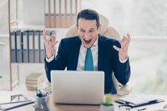 Troubled angry frustrated businessman is screaming in front of t. He monitor and gesturing sitting in modern light office Royalty Free Stock Image