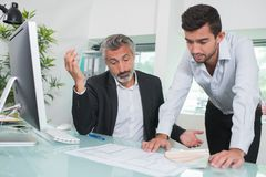 Troubled architects looking at plans in office stock photos