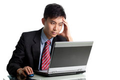 Troubled Asian businessman having a bad day. Troubled Asian businessman--Chinese/Japanese ethnicity--hit by the financial crisis at desk with laptop and a bad Stock Photo