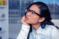 Troubled Asian woman with chin on fist Stock Image