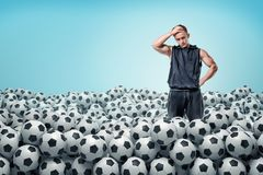 A troubled athletic man stands inside a huge heap of identical football balls. Sport trouble. Choosing best equipment. Thinking before sport game stock images