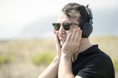 Troubled, attractive man wearing sunglasses and listening to mus. Troubled, young, attractive man wearing sunglasses and headphones royalty free stock photos