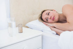Troubled blonde looking her pills Stock Photography