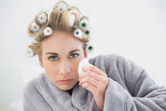 Troubled blonde woman in hair curlers crying and using tissues Stock Images