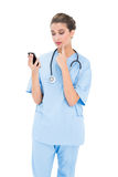 Troubled brown haired nurse in blue scrubs using a mobile phone Stock Photos